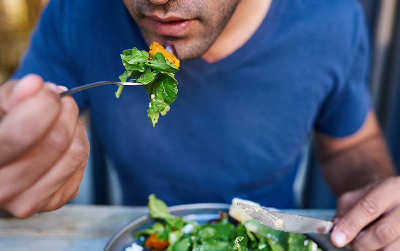 man eating leafy green salad full of vitamin b